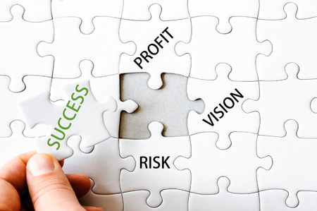 final piece of puzzle: Hand with missing jigsaw puzzle piece. Word SUCCESS. Business concept image for completing the final puzzle piece. Stock Photo