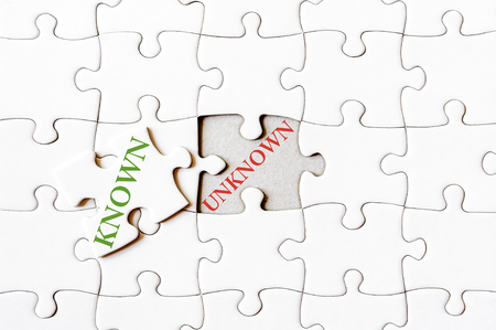 final piece of puzzle: Missing jigsaw puzzle piece with word KNOWN, covering text UNKNOWN. Business concept image for completing the final puzzle piece.