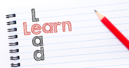 learn and lead: Learn Lead crossword written on notebook page, red pencil on the right Stock Photo