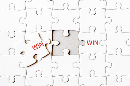 final piece of puzzle: Missing jigsaw puzzle piece completing word WIN WIN. Business concept image for completing the final puzzle piece. Stock Photo