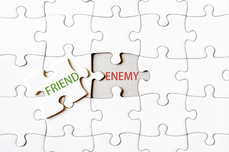 enemy: Missing jigsaw puzzle piece with word FRIEND, covering text ENEMY. Business concept image for completing the final puzzle piece.