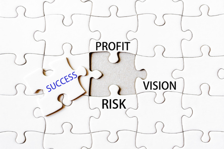 final piece of puzzle: Missing jigsaw puzzle piece with word SUCCESS between PROFIT, RISK, VISION. Business concept image for completing the final puzzle piece. Stock Photo