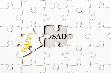 final piece of puzzle: Missing jigsaw puzzle piece with word HAPPY, covering text SAD. Business concept image for completing the final puzzle piece. Stock Photo