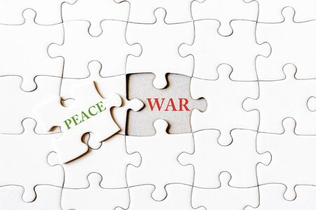 final piece of puzzle: Missing jigsaw puzzle piece with word PEACE, covering text WAR. Business concept image for completing the final puzzle piece.