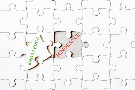 ignorance: Missing jigsaw puzzle piece with word KNOWLEDGE, covering text IGNORANCE. Business concept image for completing the final puzzle piece. Stock Photo