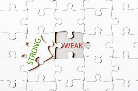 final piece of puzzle: Missing jigsaw puzzle piece with word STRONG, covering text WEAK. Business concept image for completing the final puzzle piece.