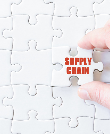 Missing jigsaw puzzle piece with word  SUPPLY CHAIN. Business concept image for completing the puzzle. Stock Photo