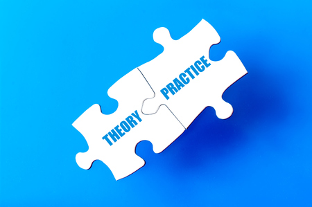 available: Connected puzzle pieces with words THEORY and PRACTICE  isolated over blue background, with copy space available Stock Photo