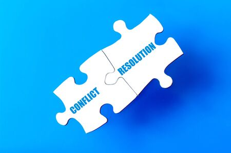 complete solution: Connected puzzle pieces with words CONFLICT and RESOLUTION  isolated over blue background, with copy space available