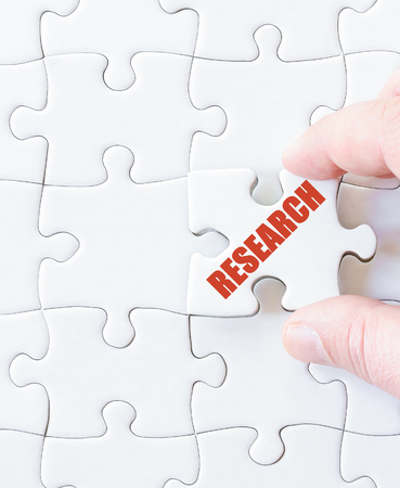 missing link: Missing jigsaw puzzle piece with word RESEARCH. Business concept image for completing the puzzle.