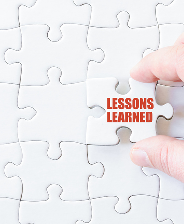 learned: Missing jigsaw puzzle piece with words LESSONS LEARNED. Business concept image for completing the puzzle.