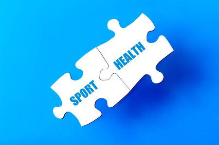 available: Connected puzzle pieces with words  SPORT and HEALTH isolated over blue background, with copy space available