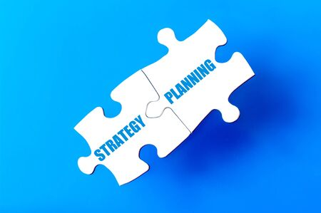 available: Connected puzzle pieces with words STRATEGY and PLANNING isolated over blue background, with copy space available