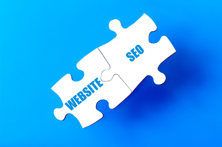 website words: Connected puzzle pieces with words WEBSITE and SEO  isolated over blue background, with copy space available