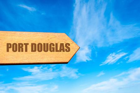 port douglas: Wooden arrow sign pointing destination PORT DOUGLAS, AUSTRALIA against clear blue sky with copy space available