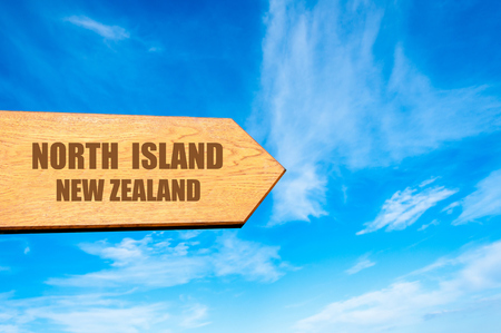 north island: Wooden arrow sign pointing destination NORTH ISLAND, NEW ZEALAND  against clear blue sky with copy space available Stock Photo