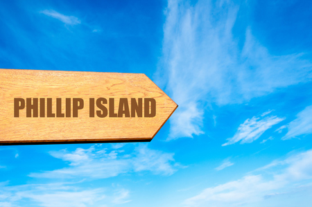 available: Wooden arrow sign pointing destination PHILLIP ISLAND, AUSTRALIA  against clear blue sky with copy space available