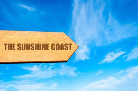 sol radiante: Muestra de madera flecha apuntando hacia el destino THE SUNSHINE COAST, AUSTRALIA contra el claro cielo azul con copia espacio disponible