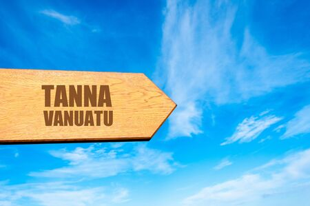 available: Wooden arrow sign pointing destination TANNA, VANUATU  against clear blue sky with copy space available Stock Photo
