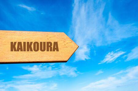 kaikoura: Wooden arrow sign pointing destination KAIKOURA, NEW ZEALAND  against clear blue sky with copy space available
