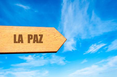 la paz: Wooden arrow sign pointing destination LA PAZ, BOLIVIA against clear blue sky with copy space available