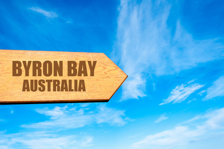 byron: Wooden arrow sign pointing destination BYRON BAY, AUSTRALIA  against clear blue sky with copy space available