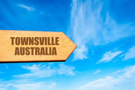 available: Wooden arrow sign pointing destination TOWNSVILLE, AUSTRALIA  against clear blue sky with copy space available