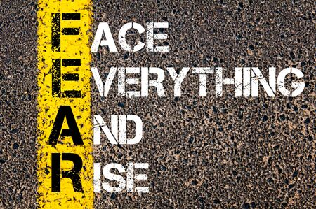 Concept image of Business Acronym FEAR as FACE EVERYTHING AND RISE written over road marking yellow paint line.