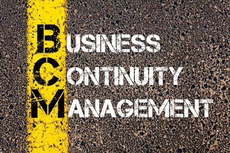 continuity: Concept image of Business Acronym BCM as BUSINESS CONTINUITY MANAGEMENT written over road marking yellow paint line.