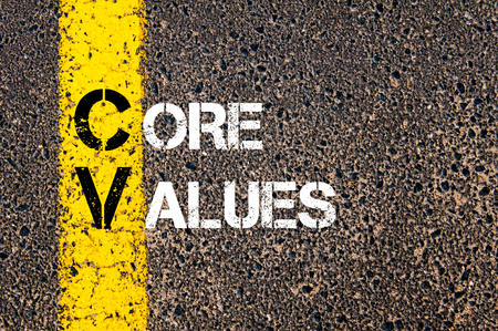 Concept image of Business Acronym CV as CORE VALUES written over road marking yellow paint line.