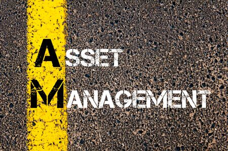 road marking: Concept image of Business Acronym AM as ASSET MANAGEMENT written over road marking yellow paint line.