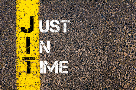 just in time: Concept image of Business Acronym JIT as JUST IN TIME  written over road marking yellow paint line.