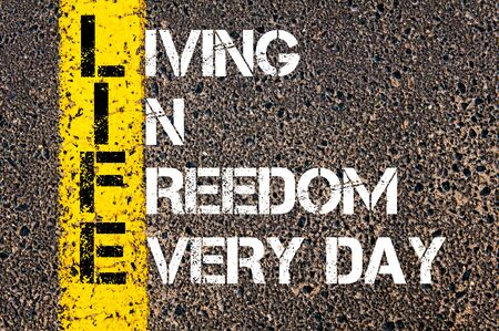 business life line: Concept image of Business Acronym LIFE as LIVING IN FREEDOM EVERY DAY written over road marking yellow paint line.