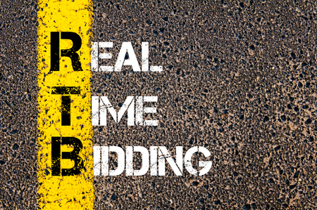 bidding: Concept image of Business Acronym RTB as REAL TIME BIDDING  written over road marking yellow paint line. Stock Photo