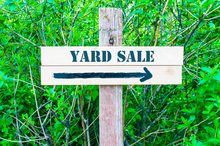 yard sign: YARD SALE written on Directional wooden sign with arrow pointing to the right against green leaves background. Concept image with available copy space