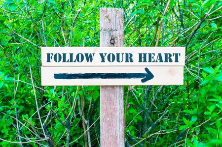 緑の葉を背景に右向きの矢印で方向の木製看板に書かれたあなたの心に従ってください。利用できるコピー スペース コンセプト イメージ