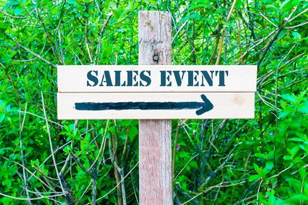 sales event: SALES EVENT written on Directional wooden sign with arrow pointing to the right against green leaves background. Concept image with available copy space
