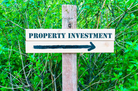 property investment: PROPERTY INVESTMENT written on Directional wooden sign with arrow pointing to the right against green leaves background. Concept image with available copy space