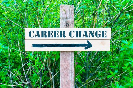 change direction: CAREER CHANGE written on Directional wooden sign with arrow pointing to the right against green leaves background. Concept image with available copy space Stock Photo