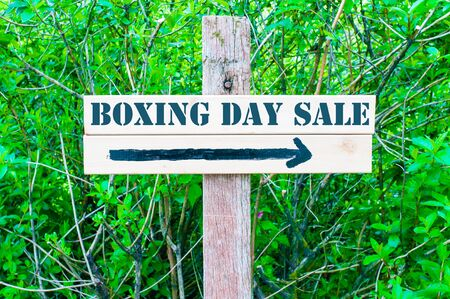 boxing day sale: BOXING DAY SALE  written on Directional wooden sign with arrow pointing to the right against green leaves background. Concept image with available copy space
