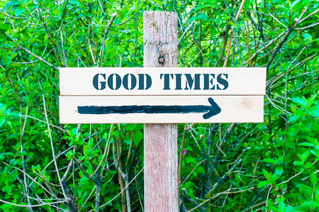 good times: GOOD TIMES written on Directional wooden sign with arrow pointing to the right against green leaves background. Concept image with available copy space Stock Photo