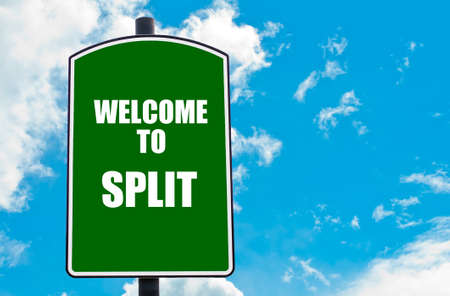 split road: Green road sign with greeting message WELCOME TO SPLIT isolated over clear blue sky background with available copy space. Travel destination concept  image