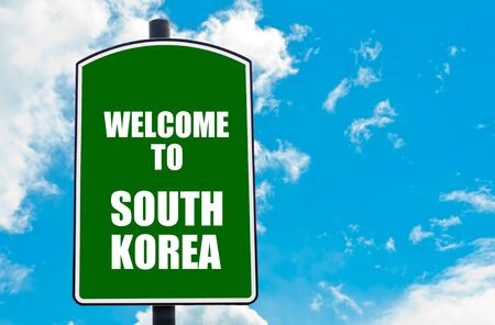 south space: Green road sign with greeting message WELCOME TO SOUTH KOREA isolated over clear blue sky background with available copy space. Travel destination concept  image