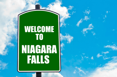niagara falls city: Green road sign with greeting message Welcome to NIAGARA FALLS isolated over clear blue sky background with available copy space. Travel destination concept  image