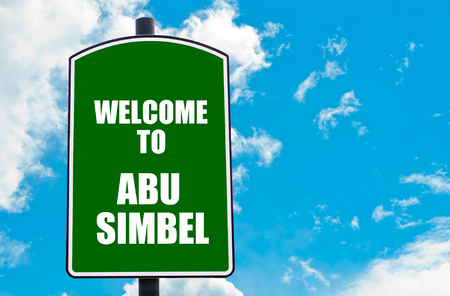 abu simbel: Green road sign with greeting message WELCOME TO ABU SIMBEL isolated over clear blue sky background with available copy space. Travel destination concept  image