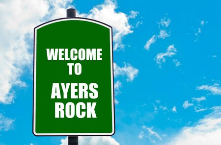 ayers: Green road sign with greeting message WELCOME TO AYERS ROCK isolated over clear blue sky background with available copy space. Travel destination concept  image Stock Photo