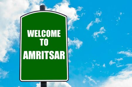 amritsar: Green road sign with greeting message WELCOME TO AMRITSAR isolated over clear blue sky background with available copy space. Travel destination concept  image Stock Photo
