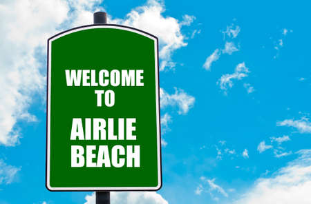 airlie: Green road sign with greeting message WELCOME TO AIRLIE BEACH isolated over clear blue sky background with available copy space. Travel destination concept  image