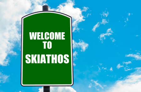 skiathos: Green road sign with greeting message WELCOME TO SKIATHOS, GREECE isolated over clear blue sky background with available copy space. Travel destination concept  image Stock Photo