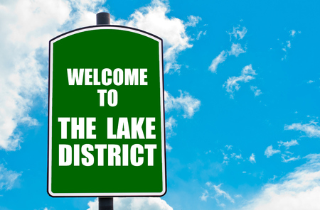 lake district england: Green road sign with greeting message WELCOME TO THE LAKE DISTRICT, ENGLAND isolated over clear blue sky background with available copy space. Travel destination concept  image